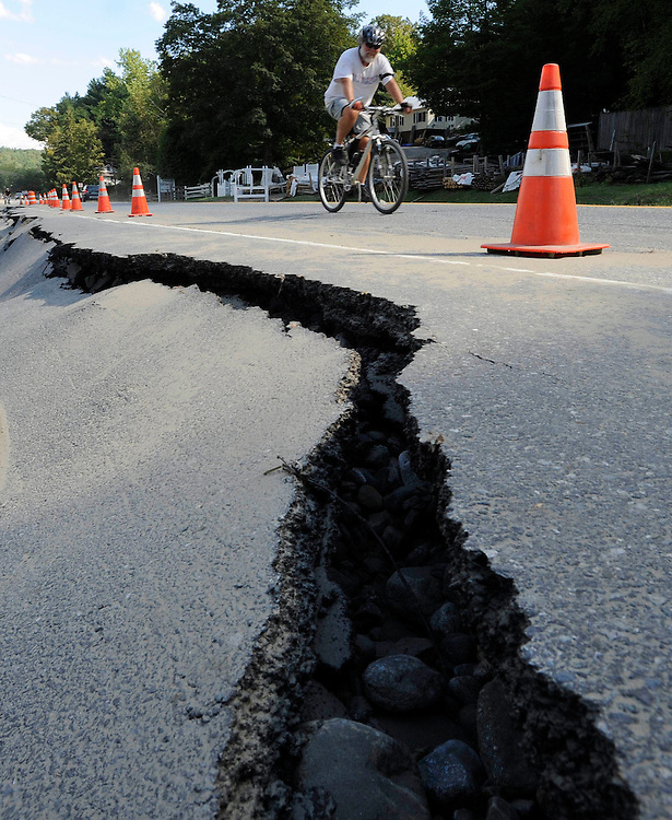 A bicyclist rides past a crack in the road along Route 9 in the aftermath of Tropical Storm Irene, in Brattleboro, Vt., Tuesday, Aug. 30, 2011. The Vermont Transportation Agency is reopening some highways that were closed because of flood damage caused by the remnants of tropical storm Irene.  (AP Photo/Jessica Hill)