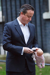 © licensed to London News Pictures. London, UK 07/01/2014. Prime minister David Cameron leaving Downing Street with his daughter Florence (not pictured) before cabinet meeting in Downing Street on Tuesday, 7 January 2014. Photo credit: Tolga Akmen/LNP