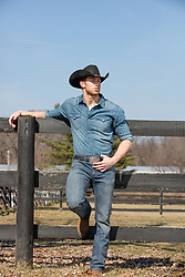 cowboy leaning on a fence