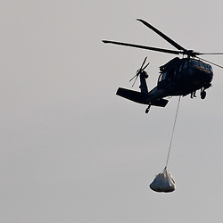 A helicopter drops 2,000 pound bags are brought to the shoreline to be used to prevent oil from reaching further into marshlands by creating a barrier off the coast west of Venice, Louisiana, U.S., on Tuesday, June 15, 2010.  Oil from Deepwater Horizon spill continues to impact areas across the coast of gulf states. (Mandatory Credit: Derick E. Hingle).