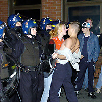 A girl gets between her boyfriend and Police in riot gear clearing the streets of Croydon, Surrey, after trouble flared following England's defeat by Portugal in Euro 2004.<br />