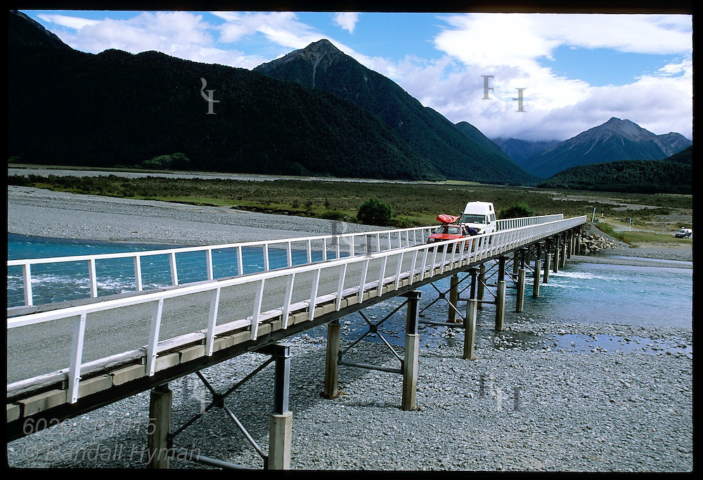 View from TranzAlpine Express in Southern Alps as it passes cars waiting on river bridge for train to pass; New Zealand.