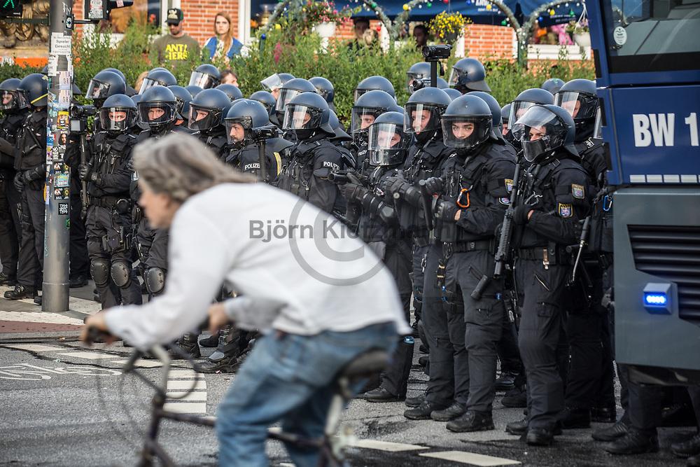 Hamburg, Germany - 07.07.2017<br /> <br /> Ein Radfahrer passiert Polizeikraefte wahrend Ausschreitungen bei den Anti G20-Protesten in Hamburg.<br /> <br /> Photo: Bjoern Kietzmann