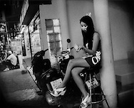 "Young woman, possibly a dancer, stationed at the entrance to a go-go bar to attract male customers on ""Walking Street"" which is lined with go-go bars and clubs.   It becomes a pedestrian street at night packed with an international throng of Thai and foreign tourists, men and women and even some children.  Pattaya, Thailand."