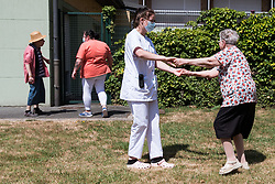 A caregiver holds a resident after meeting her daughter in a bubble at Fondation Shadet Vercoustre nursing home on May 27, 2020 in Bourbourg near Gravelines, France, where a double entry bubble has been installed to allow visits without risk of contamination, as part of a prophylactic measure against the spread of the Covid-19 disease caused by the novel coronavirus. Relatives and residents each enter the tent through a different entrance to find themselves in the same room, separated by a transparent plastic canvas. These bubbles were originally designed for tourism by the company. Photo by Julie Sebadelha/ABACAPRESS.COM