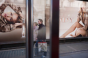A young man walks with his partner carrying a shopping bag with an image of a macho modelin front of a large ad billboard for the Body fragrance Burberry Group plc, a British luxury fashion house, manufacturing clothing, fragrance, and fashion accessories. Rosie Alice Huntington-Whiteley (born 18 April 1987) is an English model and actress unveiled as the face of Burberry's newest fragrance, Burberry Body, in July 2011 but also best known for her work for Victoria's Secret, Burberry, and her role as Carly Spencer in the 2011 film Transformers: Dark of the Moon, part of the Transformers film series