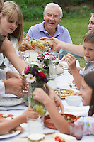 Multigenerational family dining in garden