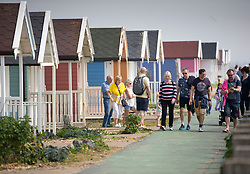 © Licensed to London News Pictures. 22/04/2019. Lancing, UK. Visitors to Lancing in West Sussex walk past coloured beach huts on the sea front as most of the UK enjoys record breaking high temperatures over the Easter weekend. Photo credit: Peter Macdiarmid/LNP