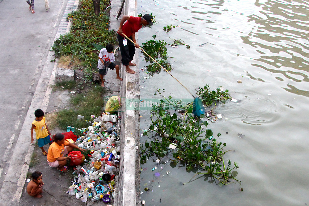 April 4, 2017 - Philippines - A man (head of the family) fishing a floating garbage in Pasig River while his family packing all the garbage's was collected and to be sold in the junkshop in Manila City on April 4, 2017. (Credit Image: © Gregorio B. Dantes Jr/Pacific Press via ZUMA Wire)