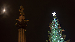 © Licensed to London News Pictures. 05/12/2019. LONDON, UK.  The moon, Nelson's column and newly lit Christmas Tree in Trafalgar Square.  The tree, a Norwegian spruce, is donated by the City of Oslo to the people of London each year as a token of gratitude for Britain's support during the Second World War.  This year, the tree has been criticised for having branches which too sparse.  Photo credit: Stephen Chung/LNP
