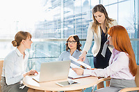 Businesswomen discussing over documents at table in office