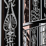 Decorative architectural details on wrought ironwork on window guard on brownstone in Greenwich Village.<br /> <br /> Products described as wrought iron, such as guard rails, garden furniture and gates, are actually made of mild steel. They retain that description because they are made to resemble objects which in the past were wrought (worked) by hand by a blacksmith (although many decorative iron objects, including fences and gates, were often cast rather than wrought).