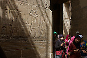 Egyptian women under sunlit hieroglyphs in the dark recesses of the ancient Egyptian Luxor Temple, Nile Valley, Egypt. The temple was built by Amenhotep III, completed by Tutankhamun then added to by Rameses II. Towards the rear is a granite shrine dedicated to Alexander the Great  and in another part, was a Roman encampment. The temple has been in almost continuous use as a place of worship right up to the present day.