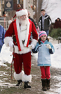 Sugar Loaf, NY - Santa Claus arrives in the crafts village of Sugar Loaf and walks on the sidewalk while holding the hand of a young girl on Dec. 12, 2009.