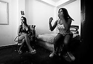 Lara Santos and Raíca watch a tv program moments before they go out to the street where they usually work.