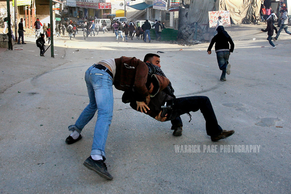 EAST JERUSALEM - FEBRUARY 9: A Palestinian youth attempts to take the gun of an undercover Israeli policeman while being arrested in the Shuafat refugee camp, February 9, 2010, in East Jerusalem.  (Photo by Warrick Page)