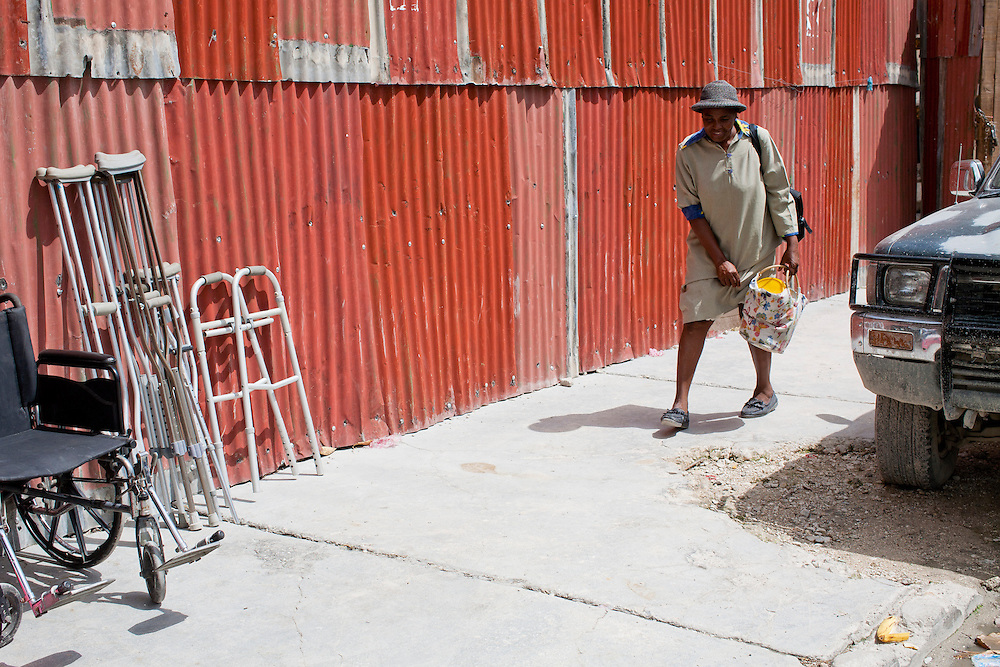 A woman passes medical equipment for sale on the sidewalk on July 7, 2010 in Port-au-Prince, Haiti.