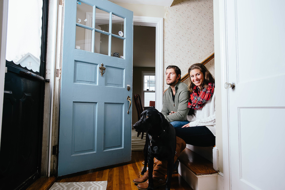 A young couple and their dog at home in Swampscott, MA, photographed for the Mass Housing Annual Report.
