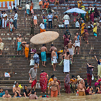 Worshippers conducting daily rituals at the ghats along the Ganges River in Varanasi, India.
