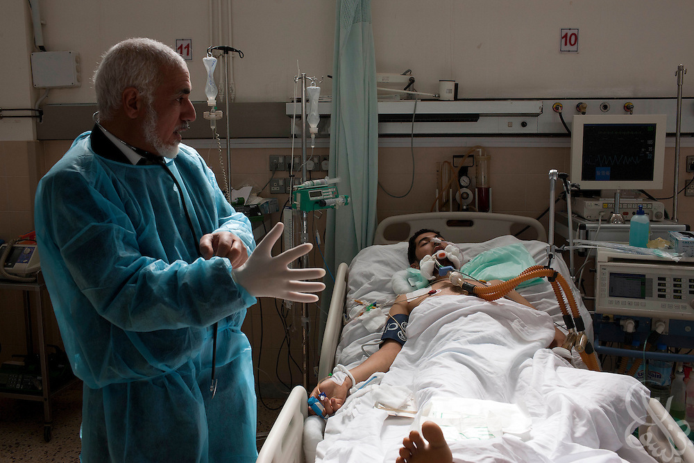 A doctor treats an intensive care unit patient February 24, 2011 at the al Jala'a hospital in Benghazi, Libya. At the height of the revolution in Benghazi during Feb. 17th-20th, doctors say the hospital treated more than 100 wounded per day. .Slug: Libya.Credit: Scott Nelson for the New York Times