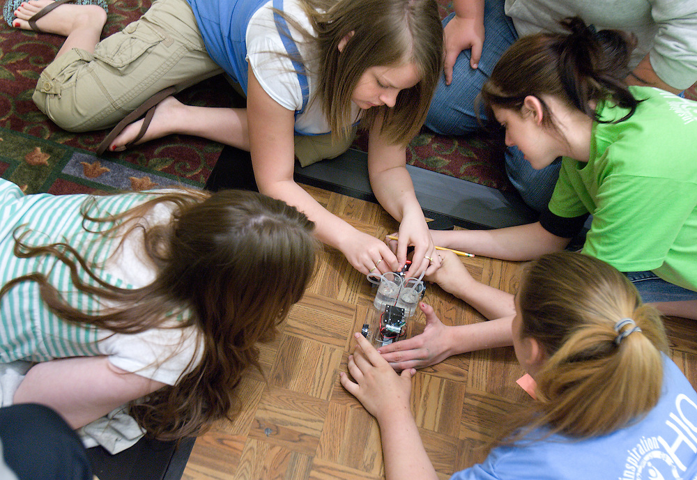 Annie Holbert, (from left), Katie Owen, Shonata Lenigar and Kayla Cline work on a battery-powered car during the Russ College of Engineering and Technology research fair/engineering day in the Baker Center ballroom on Thursday, 5/3/07.