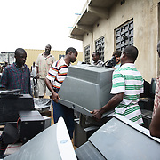 Electronic waste export to Nigeria...Alaba International Market, one of the largest markets for electronic goods in West Africa.  New and old - and a lot of non-working electronic goods such as TVs and computers come in to the market via Lagos harbour from the US, Western Europe and China...The television which was tracked by Greenpeace has been located amongst hundreds of other second hand TVs and Olayemi and his brother Kehinde, who works for Greenpeace, carry the television away.  ..The shipment - TV-set originally delivered to municipality-run collecting point in UK for discarded electronic products - was tracked and monitored by Greenpeace using a combination of GPS (Global Positioning System using satellites), GSM (positioning using data from mobile networks to triangulate approximate positions) and an onboard radiofrequency transmitter (used for making triangulations in combination with handheld directional receivers used by team on ground) is placed inside the TV-set.  The TV arrived in Lagos in container no 4629416.