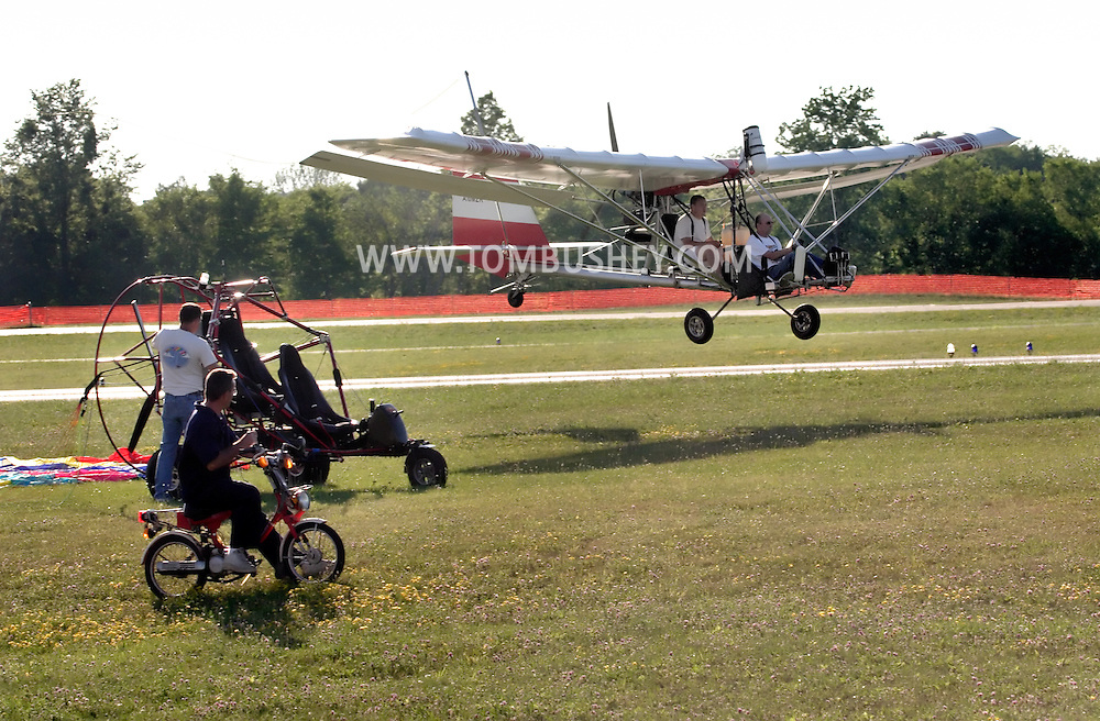 An ultralight aircraft, right, flies over Randall Airport in Middletown, N.Y., and another pilot readies his ultralight as a man on a moped looks on. July 2,2005.