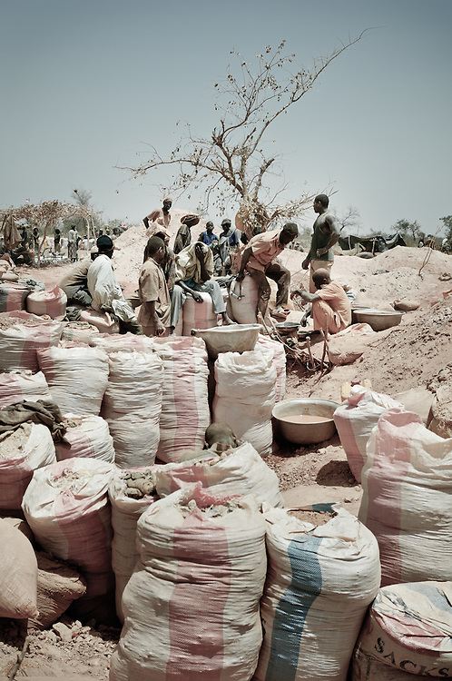 Stock photograph of African gold miners in Burkina Faso sitting on bags of gold ore under the desert sun.