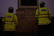 Met police riot officers with revolutionary graffiti on Nelson's Column during student protests in Trafalgar Square.