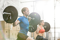 Man and woman lifting barbells in crossfit gym