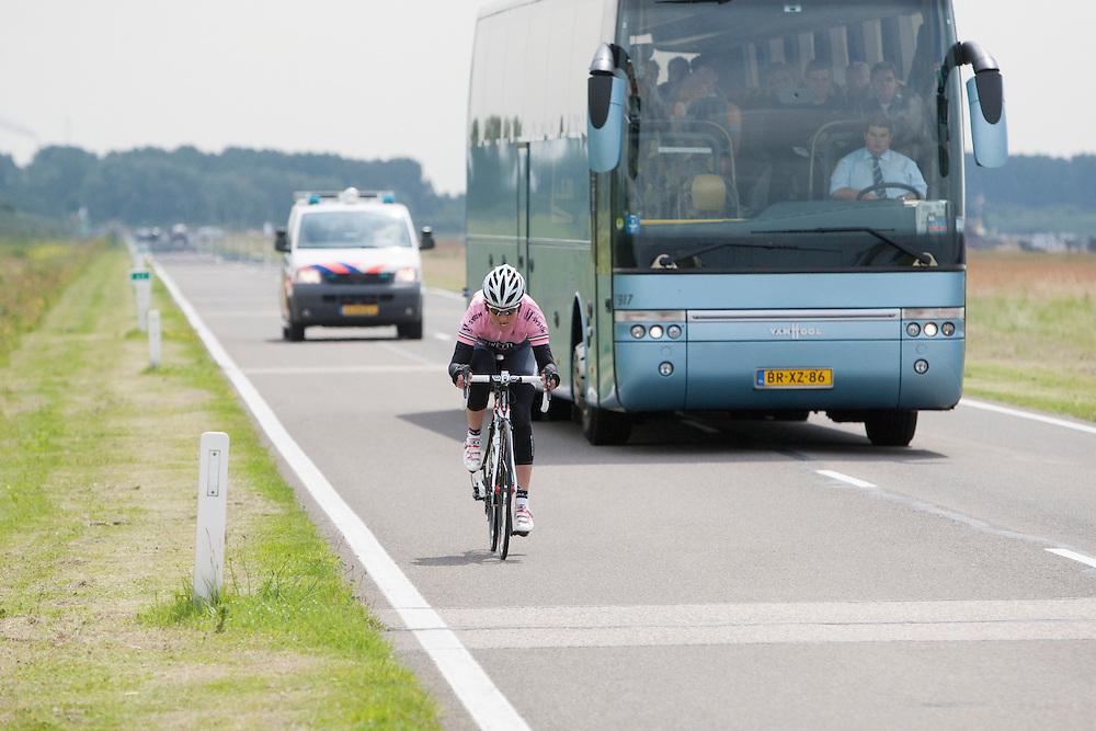 Een vrouw op een racefiets wordt ingehaald door een bus.<br /> <br /> A woman on a racing bike is passed by a bus.