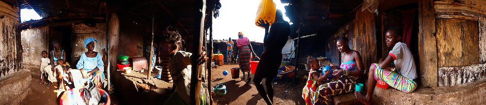 Kadija (with ball), one year old, with her mother and sister at home, Kroo Bay, Freetown, Sierra Leone.