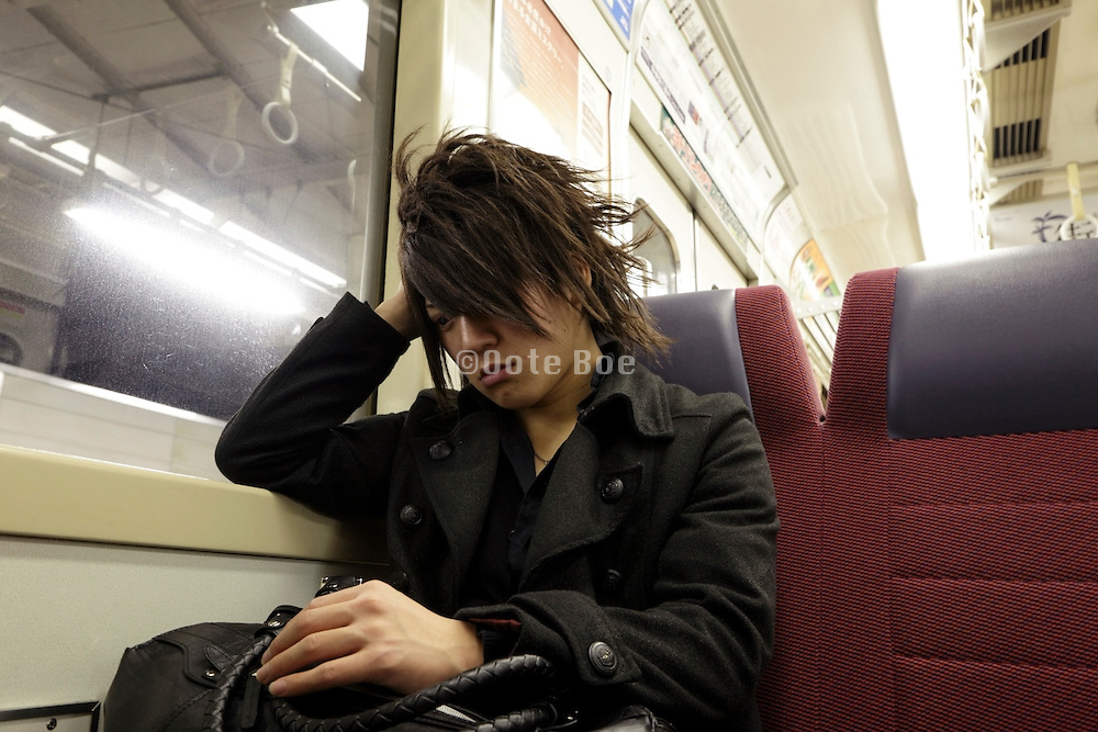 unhappy young man sitting in the train Japan