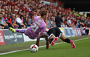Stephen Quinn (Reading midfielder) being taken out by Akaki Gogia (Brentford midfielder) during the Sky Bet Championship match between Brentford and Reading at Griffin Park, London, England on 29 August 2015. Photo by Matthew Redman.