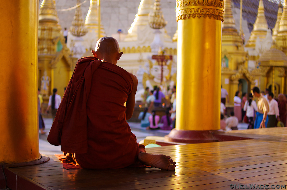 An elderly Buddhist monk meditates at busy Shwedagon Pagoda in Yangon (Rangoon), Myanmar (Burma).
