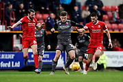 Shay McCartan of Lincoln City under pressure from James Dunne of Swindon Town and Canice Carroll of Swindon Town during the EFL Sky Bet League 2 match between Swindon Town and Lincoln City at the County Ground, Swindon, England on 12 January 2019.