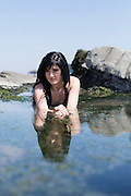 Young woman in a bikini, lying in a rockpool.
