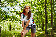 Beautiful woman hiking with backpack in the forest