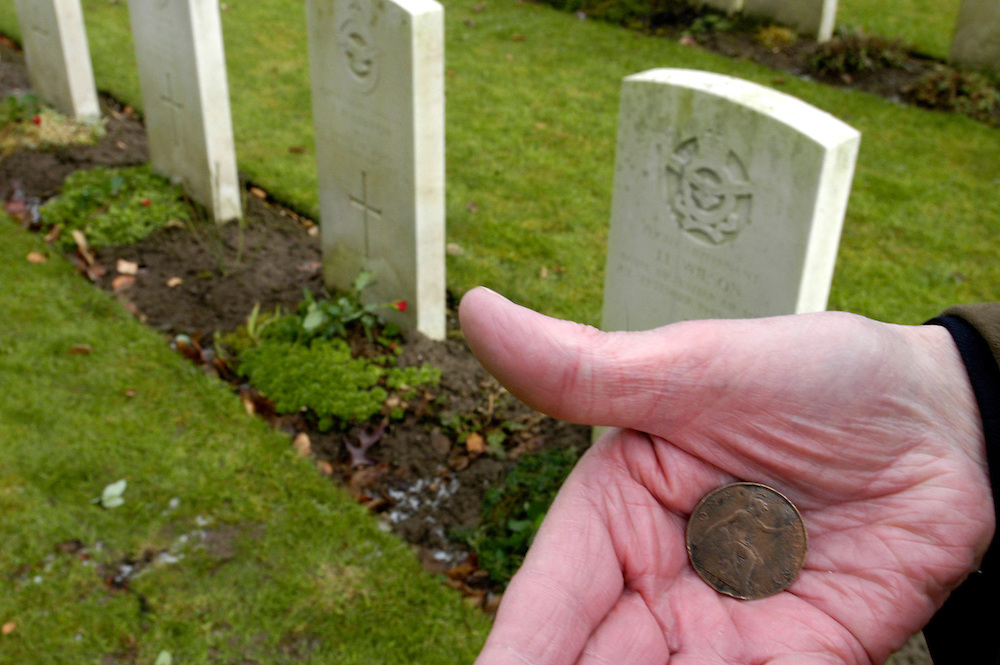 James Hopkins, Halifax Flight Engineer on his return visit to Germany. James Hopkins holds a 1914 penny found in the wreckage of his Halifax bomber, He is pictured in front of the graves of his former crew members.