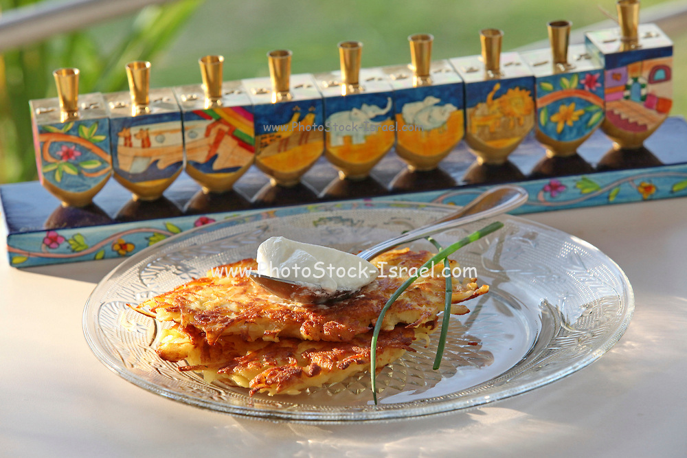 Potato pancakes (Yiddish: latkes or latkas) Traditionally eaten during Chanukkah with soar cream A Chanukkia (Chanukkah Menorah) in the background