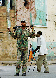 "An Angolan soldier known as ""Bernardo"" walks through the destroyed town of Kuito as a man who lost his leg to a landmine walks on crutches behind him.  Angola's brutal 26 year-civil has displaced around two million people - about a sixth of the population - and 200 die each day according to United Nations estimates. .(Photo by Ami Vitale)"