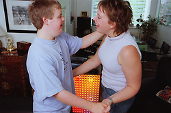 Teenage boy with Downs Syndrome dancing with sister in living room,