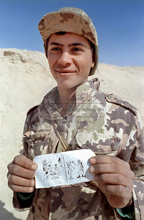An Egyptian soldier holds up an American propaganda leaflet dropped on Iraqi soldiers to persuade them to surrender along the sand berm border wall separating Kuwait from Saudi Arabia February 8, 1991 in Ar Ruqi, Saudi Arabia. The leaflets are part of a psychological operation to reduce the number of Iraqi troops and often float across the wall into coalition positions.