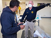 "18 MARCH 2020 - DES MOINES, IOWA: Officer BRASWELL, a security officer at the Polk County offices in downtown Des Moines, talks to a person about the new coronavirus guidelines before admitting them to the building. The county reduced its services available to the public in order to reduce the number of people coming into county buildings. County workers are screening people coming into the building, asking about recent travel and health. On Wednesday morning, 18 March, Iowa reported 29 confirmed cases of the Coronavirus. Restaurants, bars, movie theaters, places that draw crowds are closed for at least 30 days. There are no ""shelter in place"" orders in effect anywhere in Iowa but people are being encouraged to practice ""social distancing"" and many businesses are requiring or encouraging employees to telecommute.     PHOTO BY JACK KURTZ"