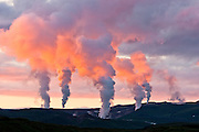 The plumes from the steaming vents of the geothermal station near Krafla are colored red by the light of the setting sun