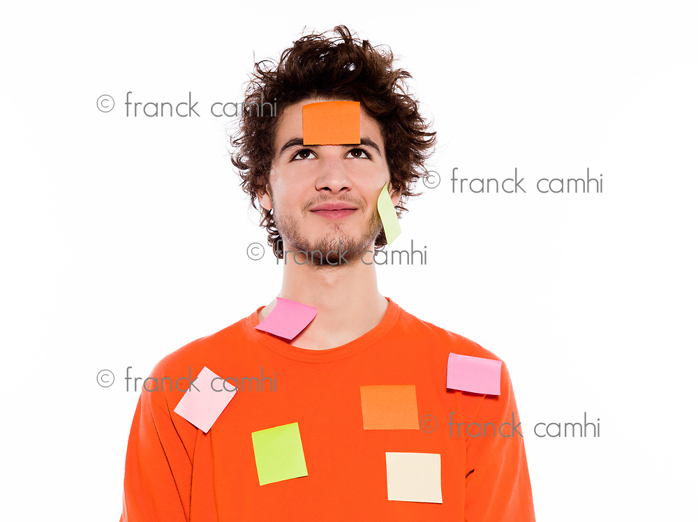 one young thinking with adhesive notes covering caucasian man portrait in studio on isolated white background