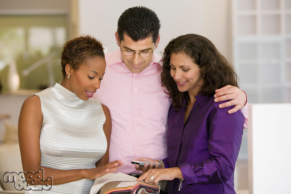 Saleswoman and Couple Examining Fabric Swatches