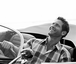 Man smiling while driving a convertible car