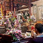 Man holds his hands up in prayer at Matsu Temple in Tainan, Taiwan