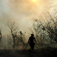 Josh Bachman/Valley Morning Star.With Smoke covering the access roads off of Expressway 77, fire crews were called in from Brownsville,San Benito and Los  Fresnos to battle a large grass fire that was started after a train threw sparks on to the grass and underbrush.